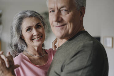 Portrait of happy senior couple dancing at home - GUSF03045