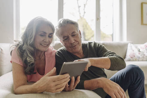Happy senior couple relaxing on couch at home using tablet - GUSF03054