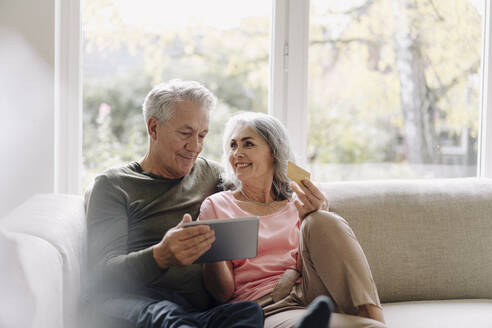 Happy senior couple relaxing on couch at home using tablet for online shopping - GUSF03057