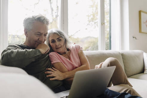 Senior couple looking at laptop on couch at home - GUSF03060