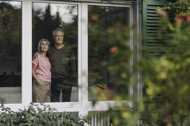Senior couple behind windowpane of their home looking out - GUSF03063