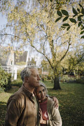 Senior couple in garden of their home in autumn - GUSF03069