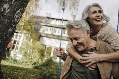 Happy woman embracing senior man on a swing in garden - GUSF03072