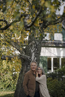Senior couple in garden of their home in autumn - GUSF03075