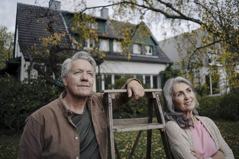 Senior couple with a ladder in garden of their home - GUSF03078