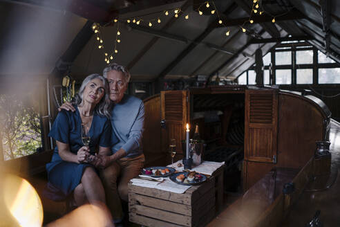 Senior couple having a candlelight dinner on a boat in boathouse - GUSF03081