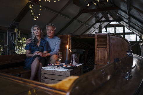 Senior couple having a candlelight dinner on a boat in boathouse - GUSF03084