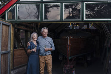 Senior couple standing in front of boathouse with glass of champagne - GUSF03087