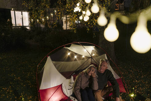 Senior couple camping in garden of their home at night - GUSF03096