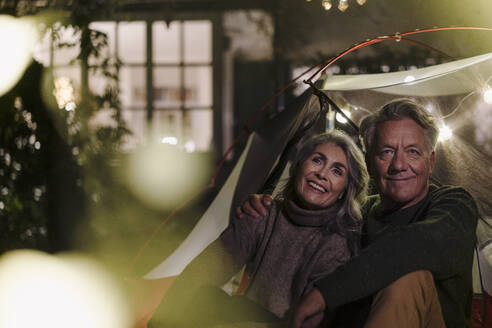 Happy senior couple camping in garden of their home at night - GUSF03099