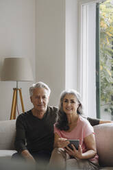Portrait of senior couple relaxing on couch at home - GUSF03108