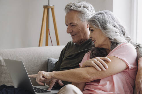 Senior couple with laptop relaxing on couch at home - GUSF03111