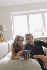 Happy senior couple relaxing on couch at home using tablet - GUSF03123