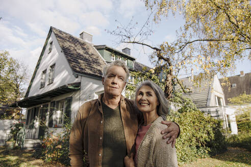 Senior couple in garden of their home in autumn - GUSF03132