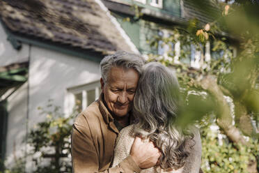 Senior man hugging his wife in garden of their home in autumn - GUSF03138