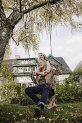 Happy woman embracing senior man on a swing in garden - GUSF03141