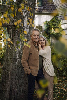 Senior couple in garden of their home in autumn - GUSF03144