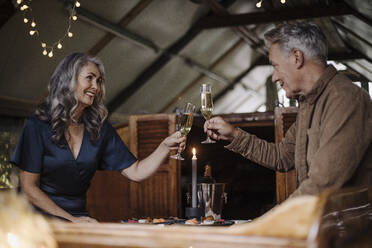 Senior couple having a candlelight dinner on a boat in boathouse clinking champagne glasses - GUSF03150