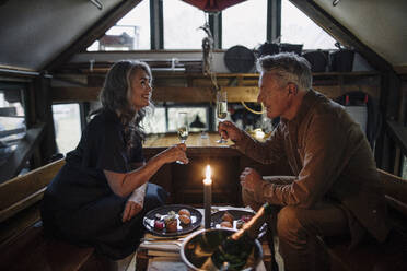 Senior couple having a candlelight dinner on a boat in boathouse clinking champagne glasses - GUSF03153