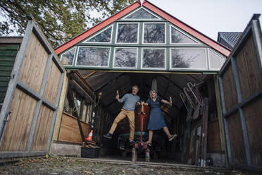 Senior couple jumping in front of boathouse with glass of champagne - GUSF03156