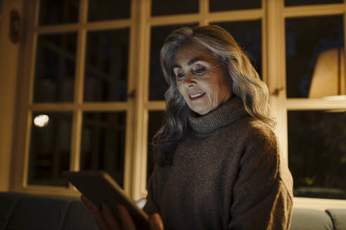 Mature woman using tablet on couch at home in the dark - GUSF03162