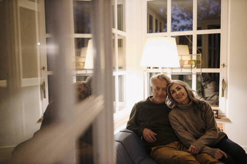 Portrait of senior couple relaxing on couch at home at night - GUSF03165