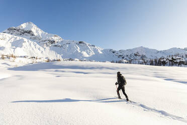 Woman walking with snowshoes in fresh snow in the mountains, Valmalenco, Italy - MRAF00475