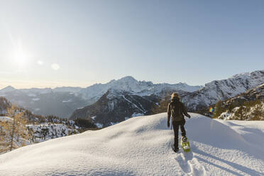 Woman walking with snowshoes in fresh snow in the mountains, Valmalenco, Italy - MRAF00478