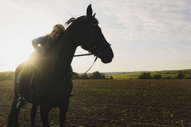 Affectionate woman on horse on a field in the countryside - JOSF04124