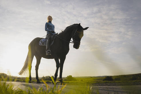 Woman on horse on a road in the countryside - JOSF04127