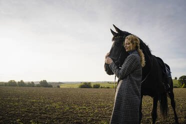 Affectionate young woman with horse on a field in the countryside - JOSF04133