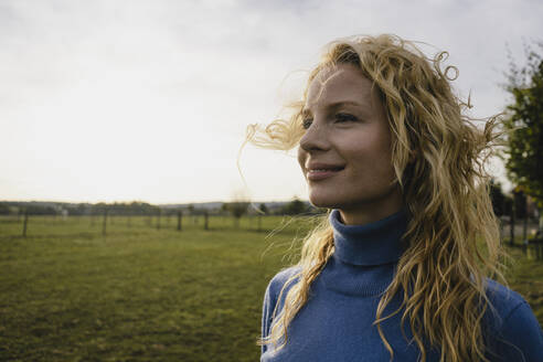 Portrait of smiling young woman in the countryside - JOSF04136