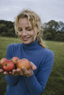 Smiling young woman holding apples in the countryside - JOSF04139