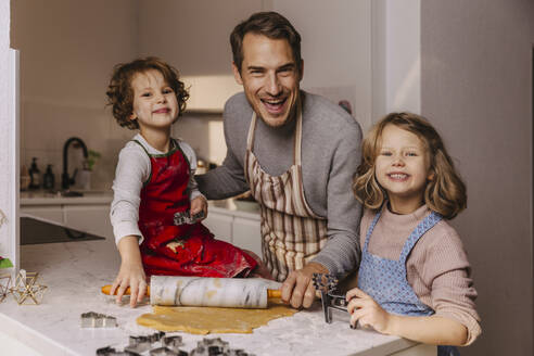 Happy father with two daughters preparing Christmas cookies in kitchen - MFF04946