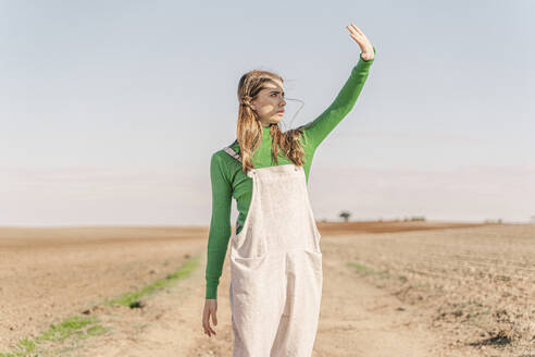 Young woman standing on dry field, shielding eyes - ERRF02296