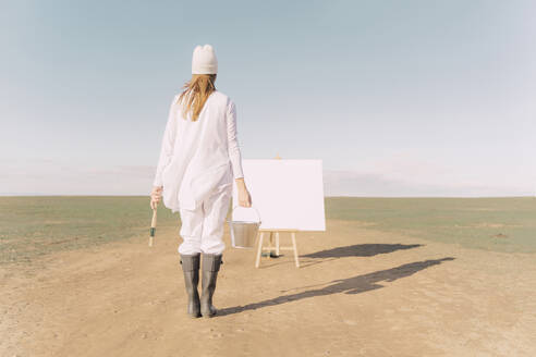 Young woman on dry field, starting to paint on white canvas - ERRF02335