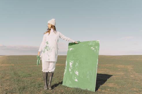Young woman holding green painting on dry field - ERRF02353