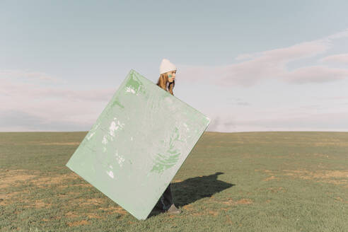 Young woman holding green painting on dry field - ERRF02383