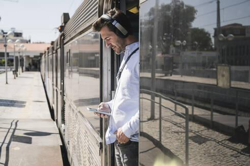 Young man with headphones and smartphone standing in train door - UUF19752