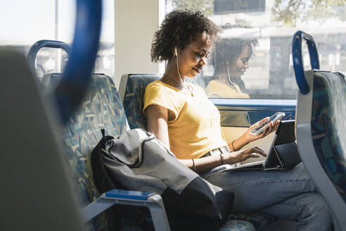 Young woman with earphones using smartphone and tablet on a train - UUF19767