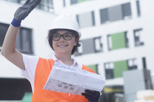 Female construction engineer with construction plan, waving - SGF02559