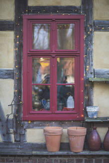 Germany, Brandenburg, Red window with Christmas lights at Christmas market - ASCF01059