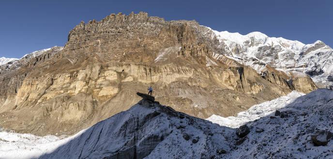 Mountaineer on top of a rock, Dhaulagiri Circuit Trek, Himalaya, Nepal - ALRF01643