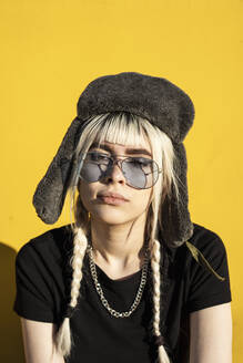 Portrait of young woman with dyed hair wearing cap and sunglasses against yellow wall - RCPF00171