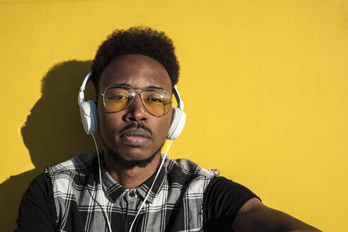 Portrait of young man listening music with headphones against yellow wall - RCPF00180