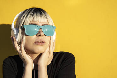 Portrait of young woman with blue sunglasses listening music in front of  yellow wall - RCPF00186