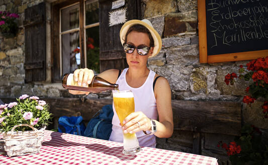 Woman pouring in a wheat beer at a mountain hut, Passeier Valley, South Tyrol, Italy - DIKF00316