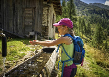 Girl refreshing with water on hiking trip, Passeier Valley, South Tyrol, Italy - DIKF00325