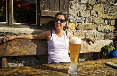 Woman enjoying the sunshine and a wheat beer at a mountain hut, Passeier Valley, South Tyrol, Italy - DIKF00328