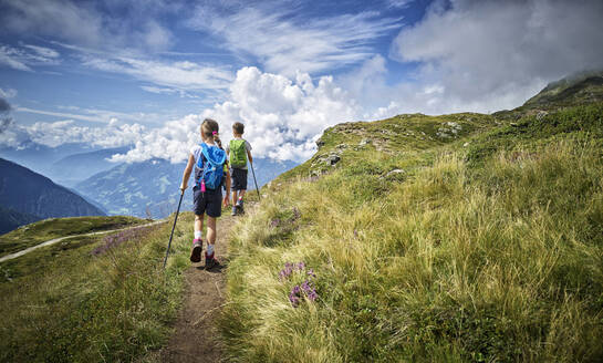 Boy and girl hiking in alpine scenery, Passeier Valley, South Tyrol, Italy - DIKF00334